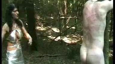 Horny mistress with trained body and big fake tits hits slave with a whip who is tied a tree